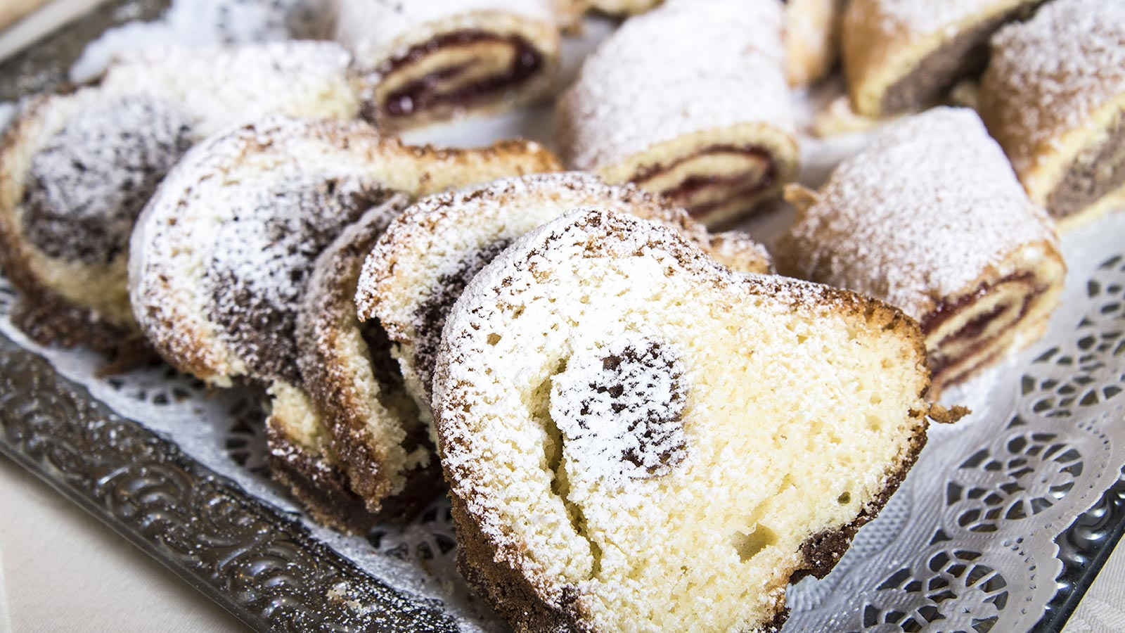 Various types of South Tyrolean desserts sprinkled with icing sugar