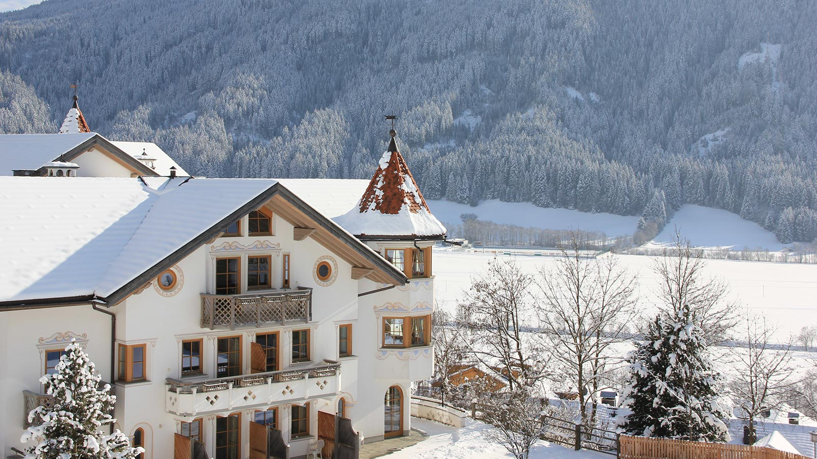 The facade of our 3-star hotel in Val Casies with its snow-capped roof on a sunny winter day.