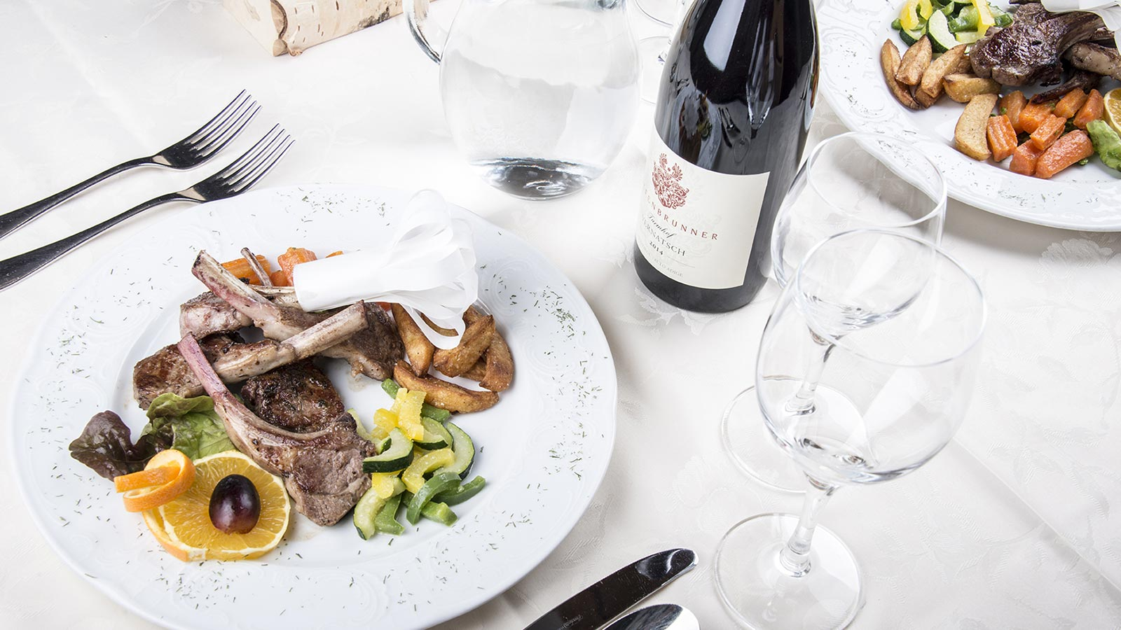 Exquisite dish with lamb ribs and vegetables accompanied by a bottle of red wine