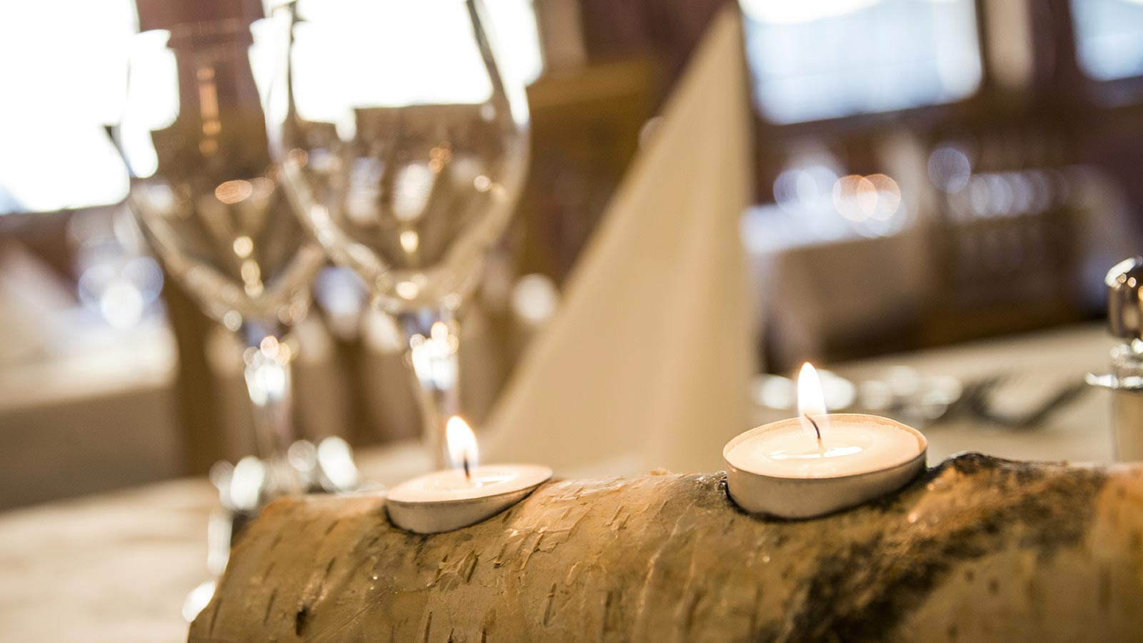 Table decoration made of wood with lighted candles and glass goblets in the background
