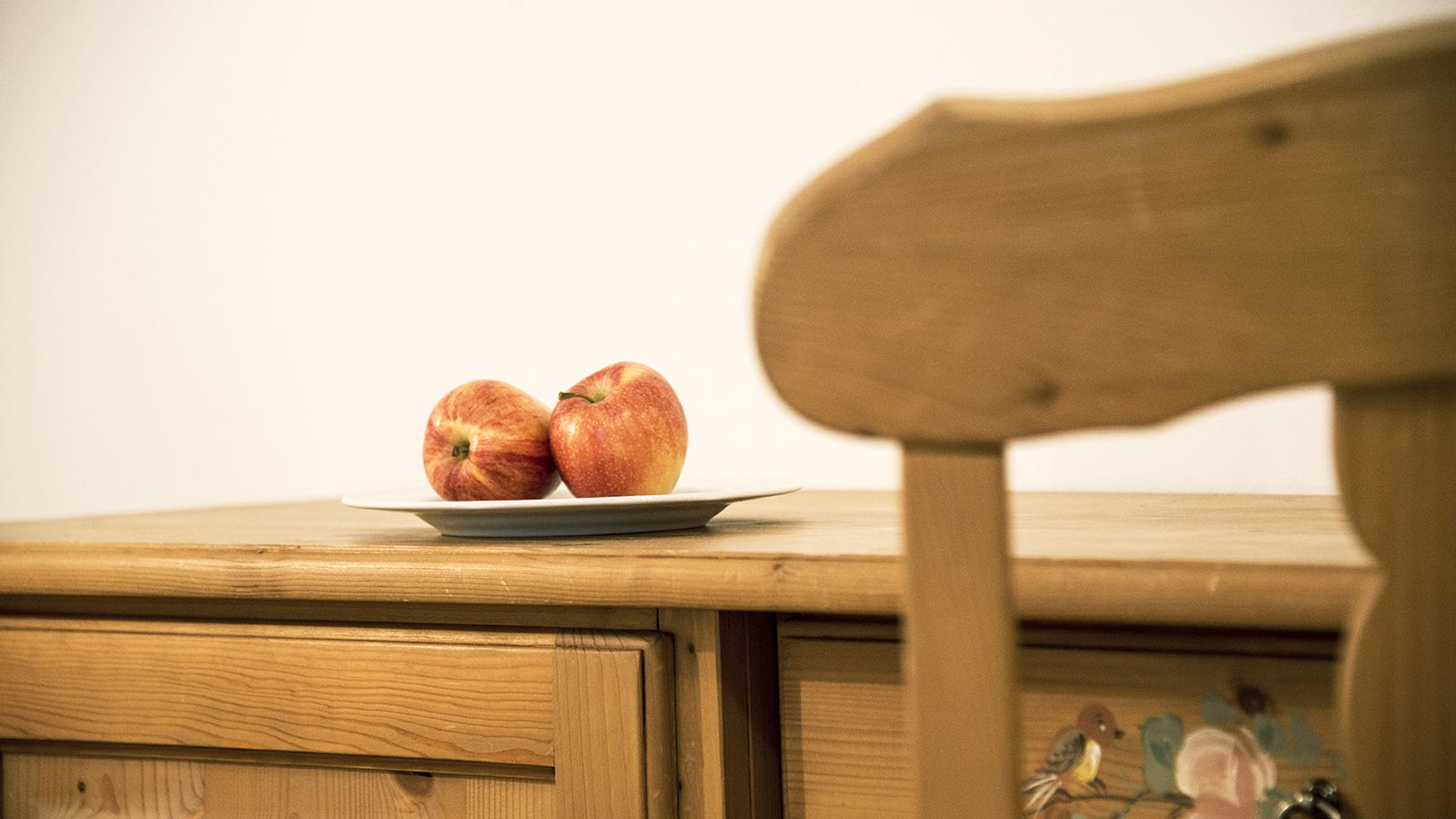 Wooden case bench, on which is placed a plate with two red apples, and blurred backrest of a wooden chair